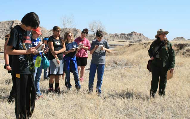 Students work on nature journals with a park ranger