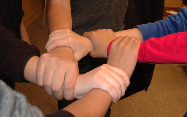 Five interlocking hands grabbing the wrist of the person next to them