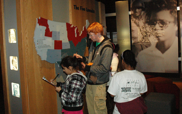 A teacher and students research answers at The Five Lawsuits exhibit.