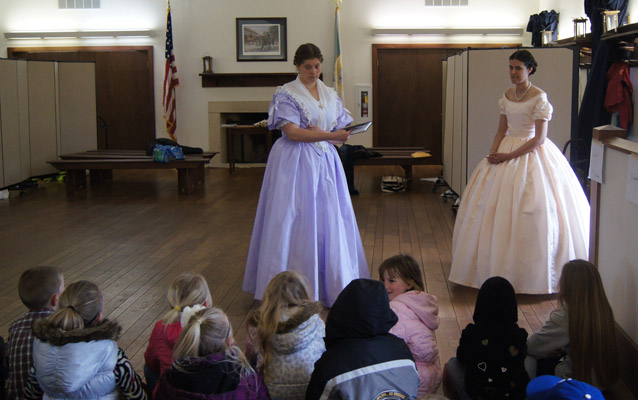 Volunteers in period clothing instructing elementary students about leisure pasttimes of the soldiers.