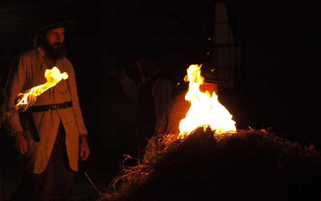 Reenactor portraying James Montgomery lighitng a wagon of hay on fire