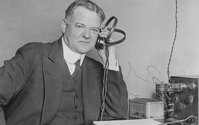 Black and white photo of Herbert Hoover in front of a radio set.