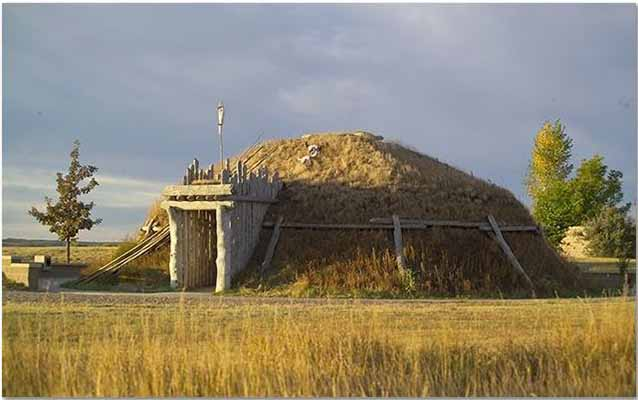 A Hidatsa Earthlodge. Structure build of wood and earth in a circular shape with a doorway extending out.