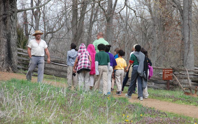 Park ranger meets educational group on the trail to the farm.