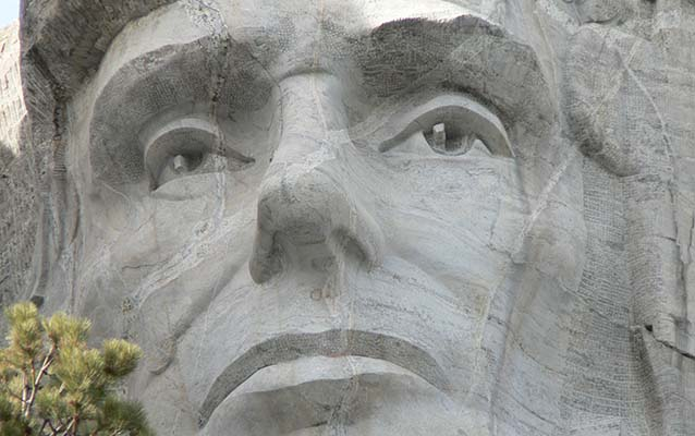 Closeup of Abraham Lincoln on Mount Rushmore with fractures running across.