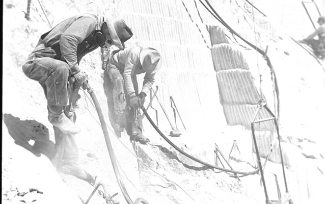 Workers drill with jackhammers on Mount Rushmore.
