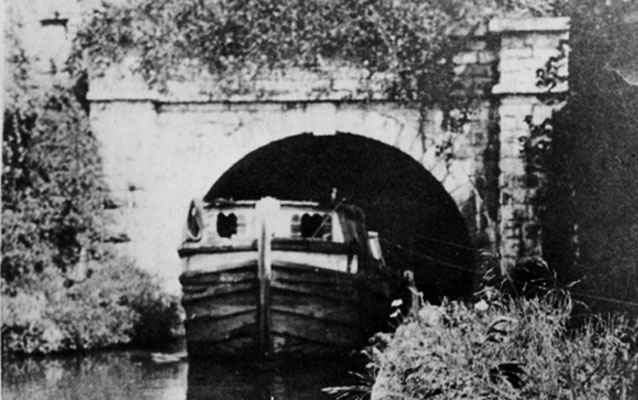 An historic black and white photo of a boat near the Paw Paw tunnel.