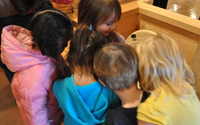 A photo of five children peeking into one of the barrels at the C&O Canal Museum at Canal Place