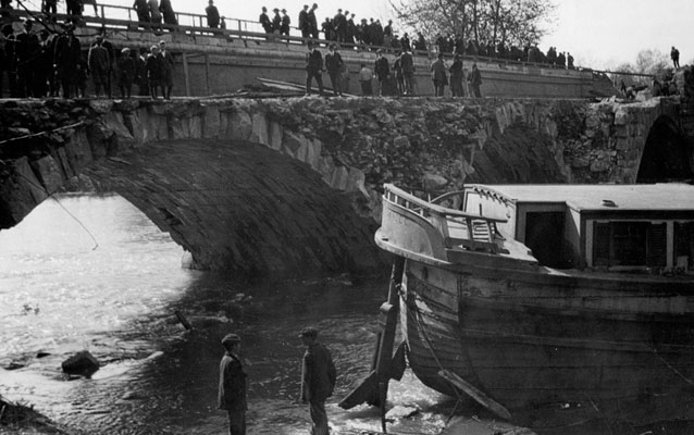 An historic, black and white photo of Captain Meyers boat in the creek below the canal aqueduct.