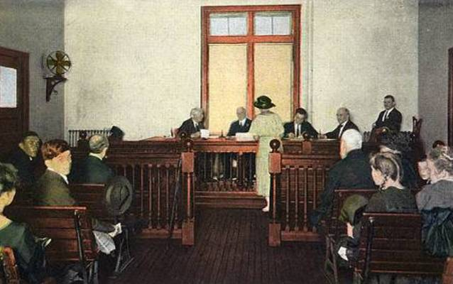 People seated in a courtroom setting with three judges at front with other officials (Photochrom image).