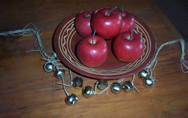 A string of jingle bells and a plate of red apples decorate a wooden table.