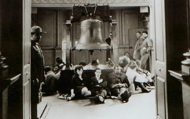 Black and white photo showing students sitting around the base of the platform supporting the Liberty Bell.