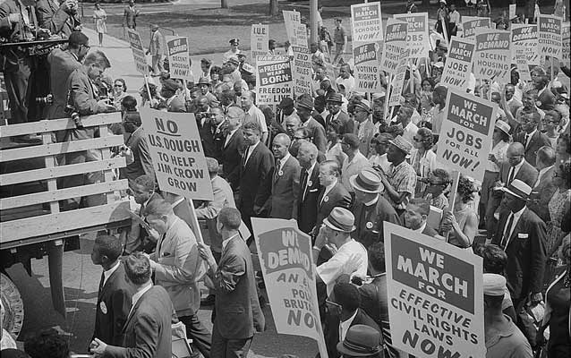 Black and white photo from the 1960's showing a large crowd walking forward and holding signs about civil rights.