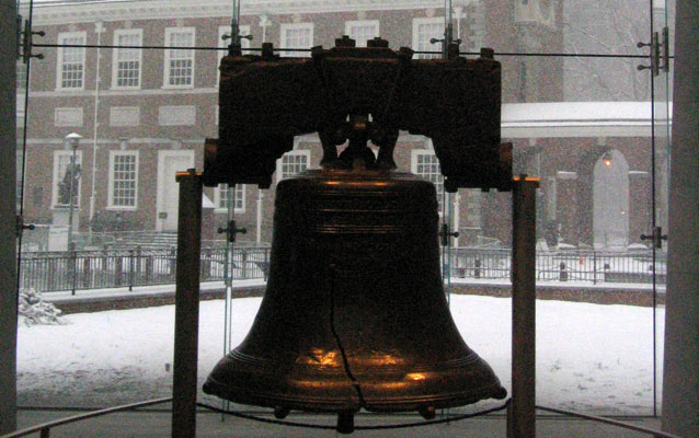 The Liberty Bell sits in the foreground with Independence Hall behind on a snowy day.