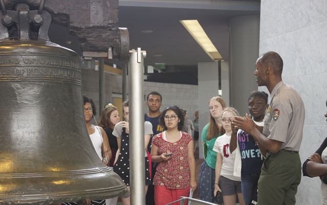 Color photo showing a male park ranger speaking to a group of teens standing in front of the Liberty Bell.