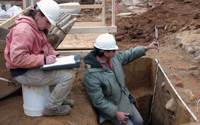 Two archeologists work at a dig site, one measuring a pit and the other writing in a notebook.