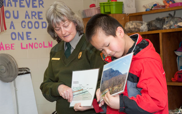 A park ranger holds up a photo while a child holds up another picture beside her.
