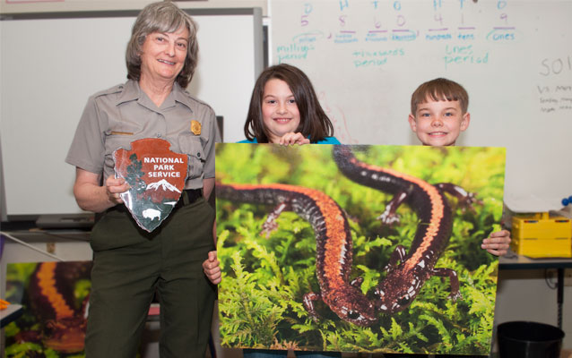 Two kids hold up a large picture of a Shenandoah Salamander next to a park ranger who holds up an arrowhead, the symbol of the National Park Service.