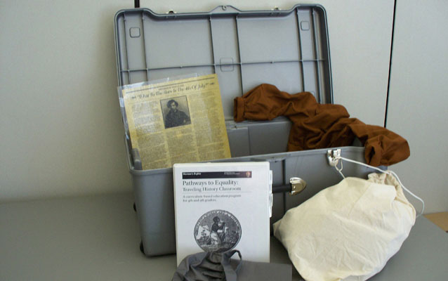 Picture of an opened Traveling Trunk with some of its contents on display.