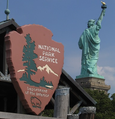 A view from the dock of the Statue of Liberty with the National Park Service arrowhead in the foreground,