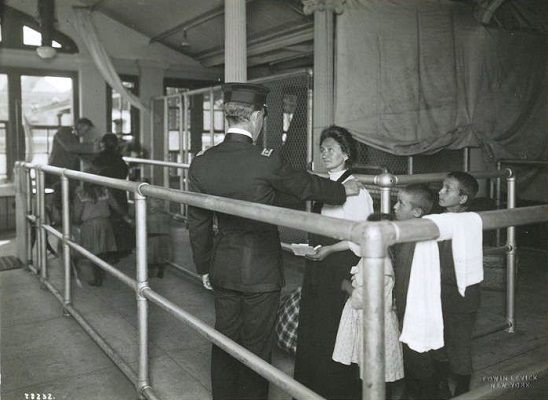 A photo circa 1911 of an immigrant family undergoing a medical examination at Ellis Island.