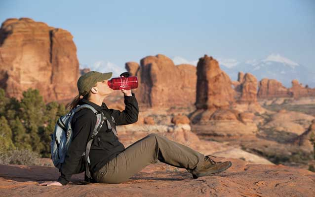 a woman drinks from a red water bottle