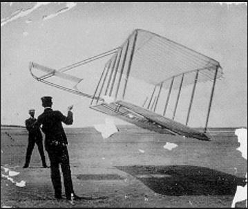 black and white photo of two men standing left wearing black suits holding ropes as they fly a large box kite