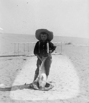photo of a young boy on a beach in front of a box kite. He has on a sun hat and his right hand on his hip. In his left he is holding a fish.