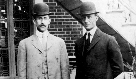 black and white photo of two men dressed in suits facing a camera in front of a brick wall and window