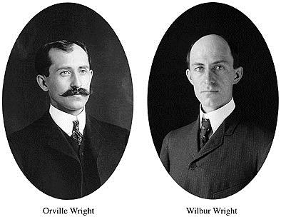 black and white portrait photos of two men in suits the left has a mustache the right is clean shaven.