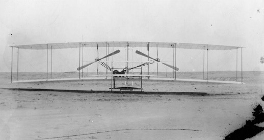 black and white photo of a bi-wing plane sitting on a stretch of sand