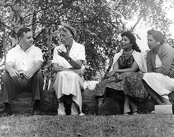 A man and three women sitting on a log outdoors in conversation.