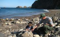 Park ranger wtih child on beach.