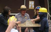 Teachers and students use a volcano model with a park ranger