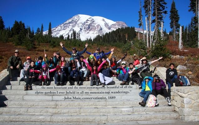 A Mount Rainier Institute student group poses in front of Mount Rainier on the steps near the Jackson Visitor Center in Paradise.