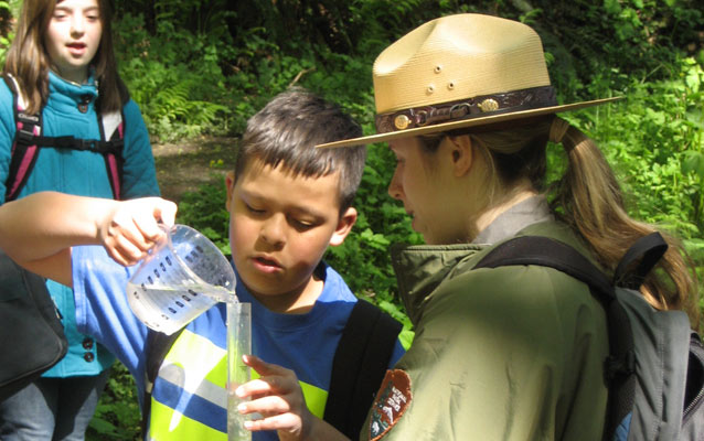 A ranger assists a student demonstrating how to measure water turbidity.