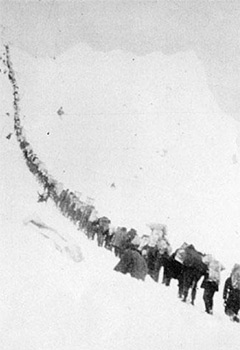 historic image of a long line of stampeders waiting to hike up a steep slope