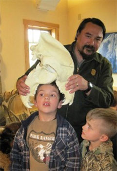 a ranger shares a bear skull with two kids.