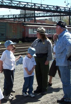 A Park Ranger and a steam locomotive engineer chat with school students in the rail yards.