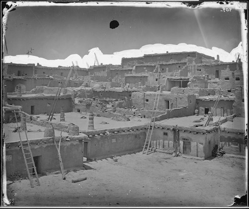 Black and white photo of Zuni Pueblo, earthen architecture with wooden ladders