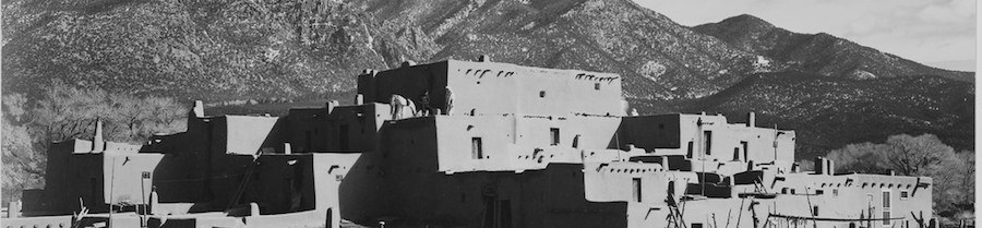 A pueblo of adobe and rock with snow capped mountains in the background