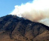 Smoke rising over ridge as fire starts to crest Bob Thompson Peak.