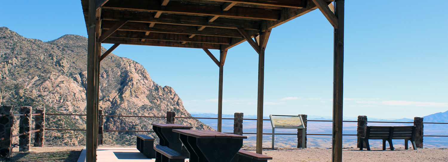 A ramada structure with tables at a mountain overlook