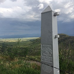 An obelisk marking the US-Mexico border with hills in Mexico in the background