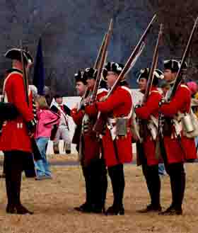 Reenactors portraying British soldiers prepare to drill.