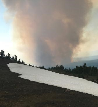 a smoke plume rising above as snow field