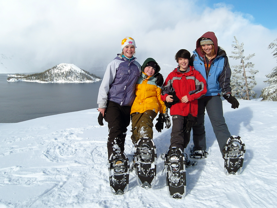 Kids pose in front of Crater Lake on a ranger-guided snowshoe walk.