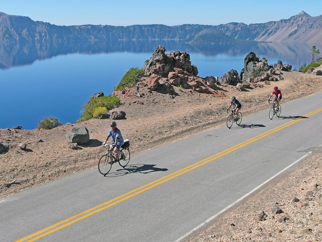 Bicyclists riding along East Rim Drive with view of Crater Lake in the background.