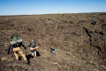 backpackers crossing lava