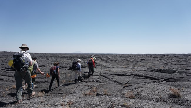 scientists hiking on lava